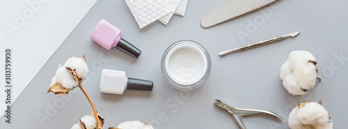 Stylish trendy manicure accessories with gel nail polishes, scissors, cuticle pusher, cotton and eucalyptus flowers. Horizontal web banner. Flat lay, top view, mock up, copy space template, overhead