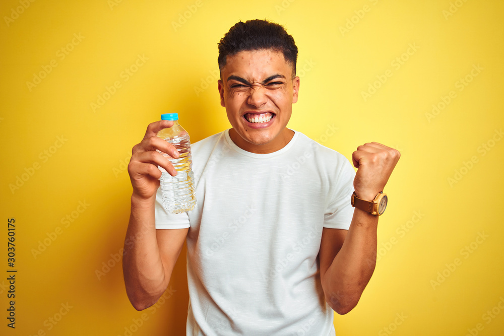 Fototapeta Young brazilian man holding bottle of water standing over isolated yellow background screaming proud and celebrating victory and success very excited, cheering emotion