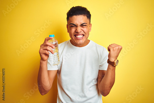 Obraz Young brazilian man holding bottle of water standing over isolated yellow background screaming proud and celebrating victory and success very excited, cheering emotion - fototapety do salonu
