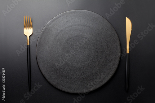 Fotografía Empty black plate with fork and knife on black background