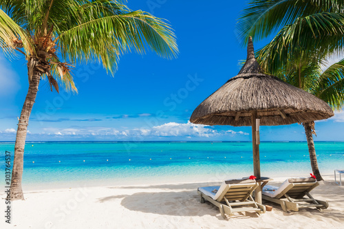 Chairs and umbrella at sandy beach with palms. Holiday banner