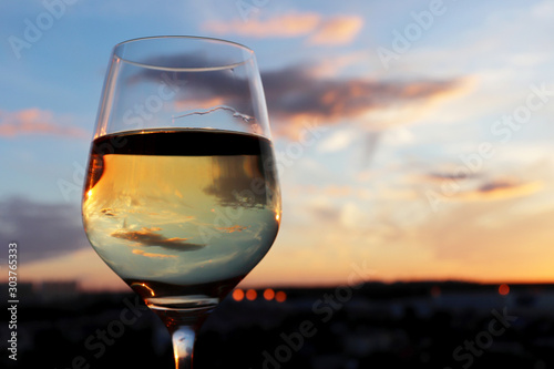 Foto auf Leinwand Alkohol Glass of white wine on colorful sunset background, sun and sky are reflected in alcohol drink. Concept of celebration, evening party at resort, romantic dinner outdoors