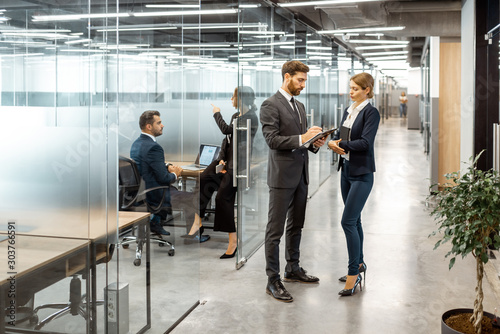 Fotografie, Obraz  Business people talking in the hallway of the modern office building with employees working behind glass partitions