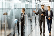 Business people walking in the hallway of the modern office building with employees working behind glass partitions. Work in a large business corporation