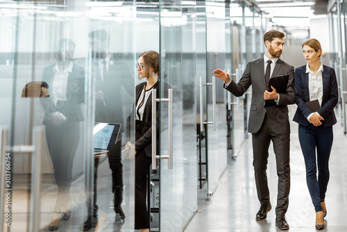 Fototapety, obrazy: Business people walking in the hallway of the modern office building with employees working behind glass partitions. Work in a large business corporation