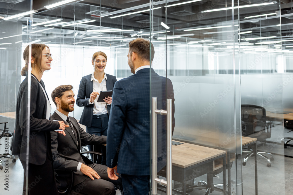 Fototapeta Group of strictly dressed business people having a discussion, sitting at the workplace with a computer in the modern office with glass partitions