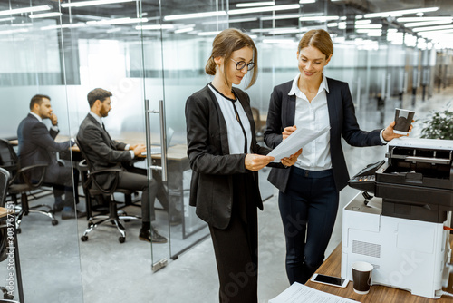 Fototapety, obrazy: Two business ladies talking near the copier during a coffee break in the hallway of the big corporation