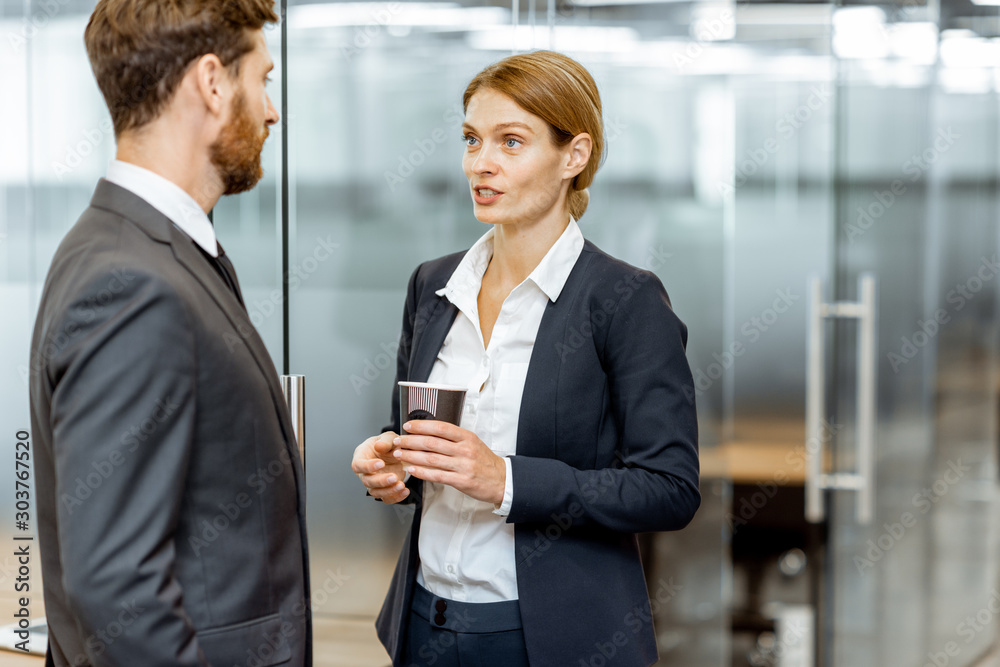 Fototapeta Business man and woman meeting in the hallway of the modern office building, white-collar workers having informal discussion