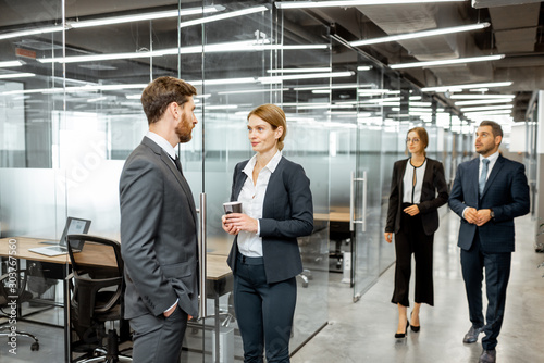 Fototapety, obrazy: Business man and woman meeting in the hallway of the modern office building, white-collar workers having informal discussion