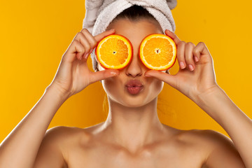 Young beautiful woman with towel on her head holding slices of orange in fron...