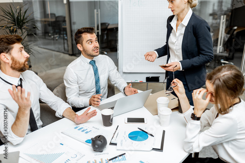 Fototapety, obrazy: Female top manager or team leader quarreling at employees, dissatisfied with their work during a conference in the meeting room