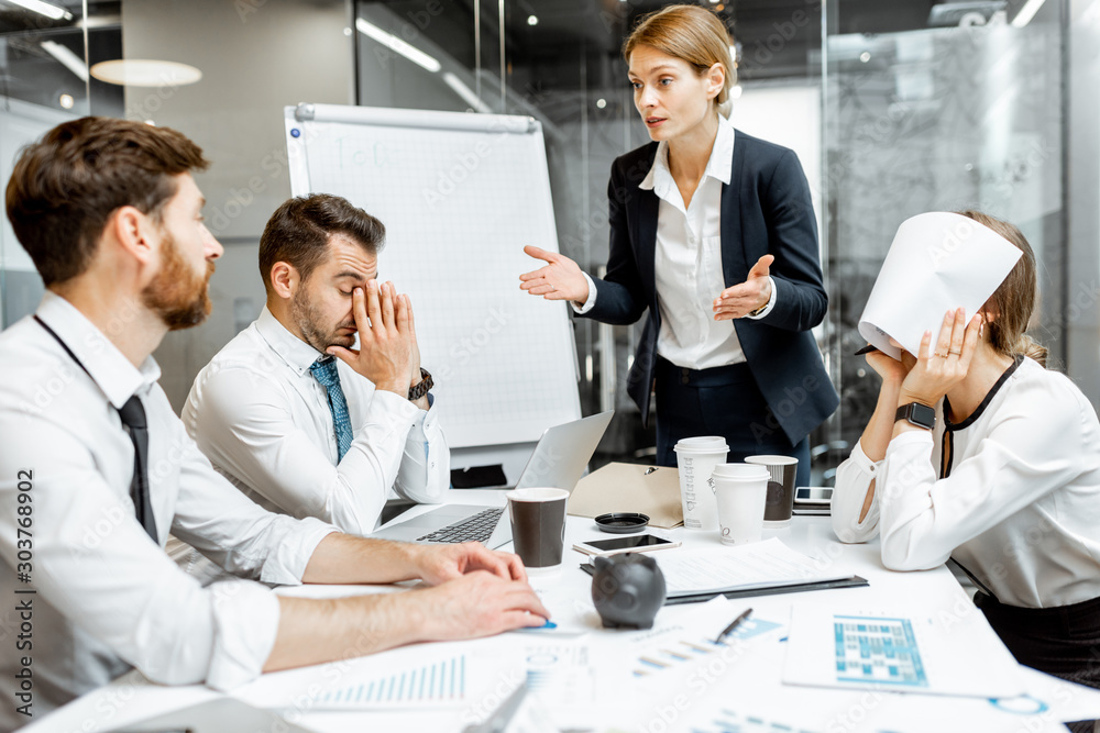 Fototapeta Female top manager or team leader quarreling at employees, dissatisfied with their work during a conference in the meeting room