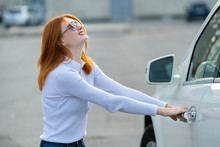 A Woman Trying To Open Closed Car Doors.