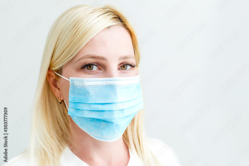 Fototapeta woman with a medical mask for protection again influenza. Shallow depth of field. Copy space for your text.