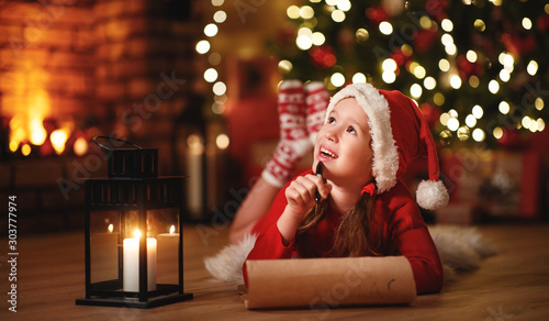 Poster de jardin Akt happy child girl writing letter santa home near Christmas tree.