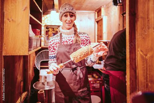 Baker on the Christmas market selling sweet cakes