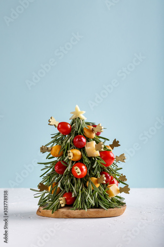 Christmas edible tree made from cheese, vegetables and sprigs of rosemary. New Year food background, food art concept. Copy space.