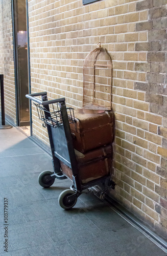London, United Kingdom - August 26, 2018: Platform 9 and 3/4 at Kings Cross Station, London. A trolly stuck in the wall where fans emulate the Harry Potter adventures.