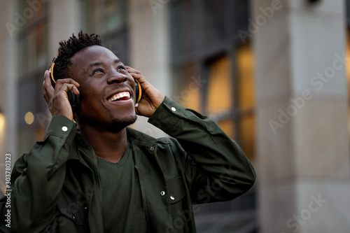 happy african-american man in stylish jacket in wireless headphones listening music on the street of the evening city. space for text - 303780323