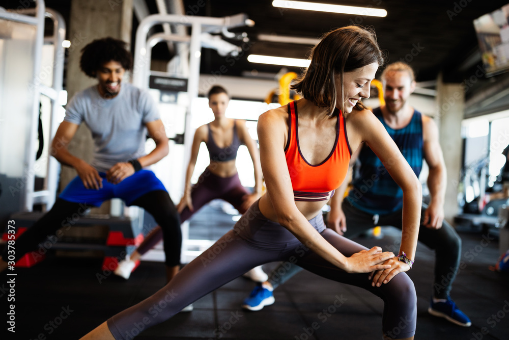 Fototapeta Attractive sports people are working out in gym