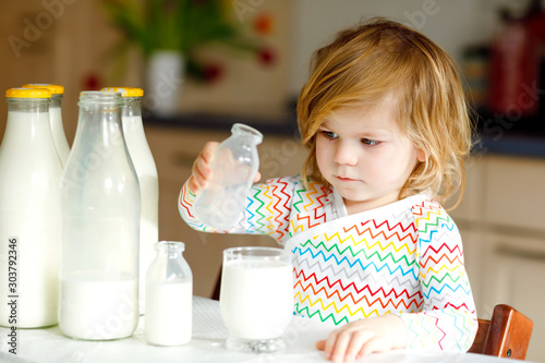 Adorable toddler girl drinking cow milk for breakfast Canvas Print