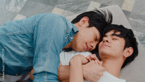 Young Asian gay couple sleep together at home Wallpaper Mural