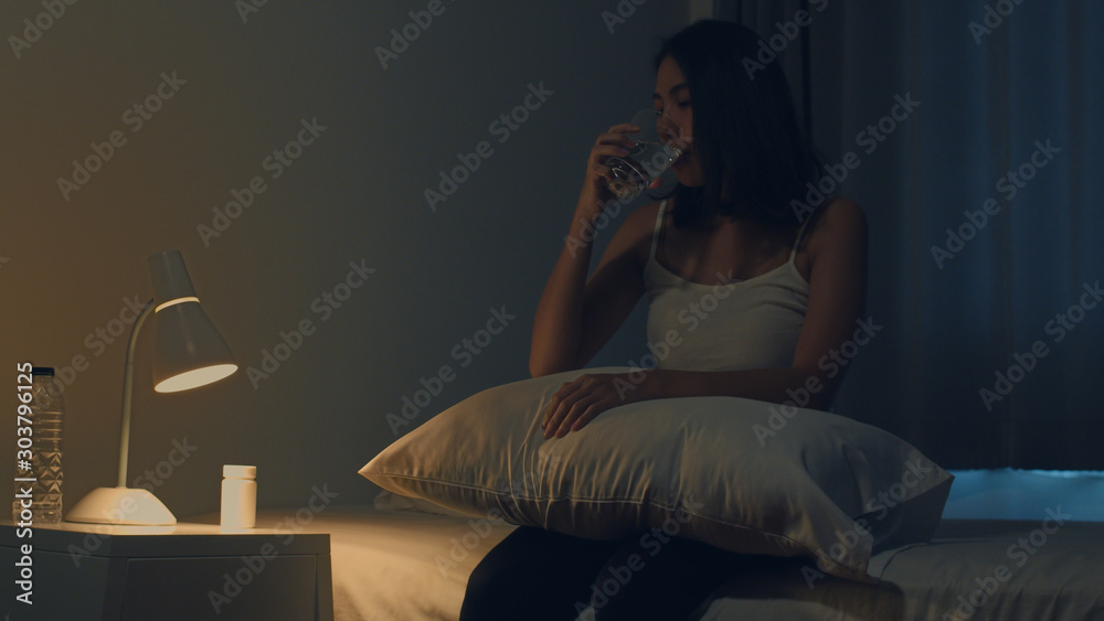 Fototapety, obrazy: Beautiful Asian young woman sitting on bed take sleeping pill or night medicine in bedroom. Unhealthy sick Indian female suffers from insomnia or headache, depressed girl holds antidepressant meds.