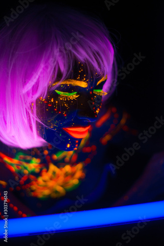 Portrait of Beautiful Fashion Woman in Neon UF Light. Model Girl with Fluorescent Creative Psychedelic MakeUp, Art Design of Female Disco Dancer Model in UV, Colorful Abstract Make-Up. Dancing Lady - 303796143
