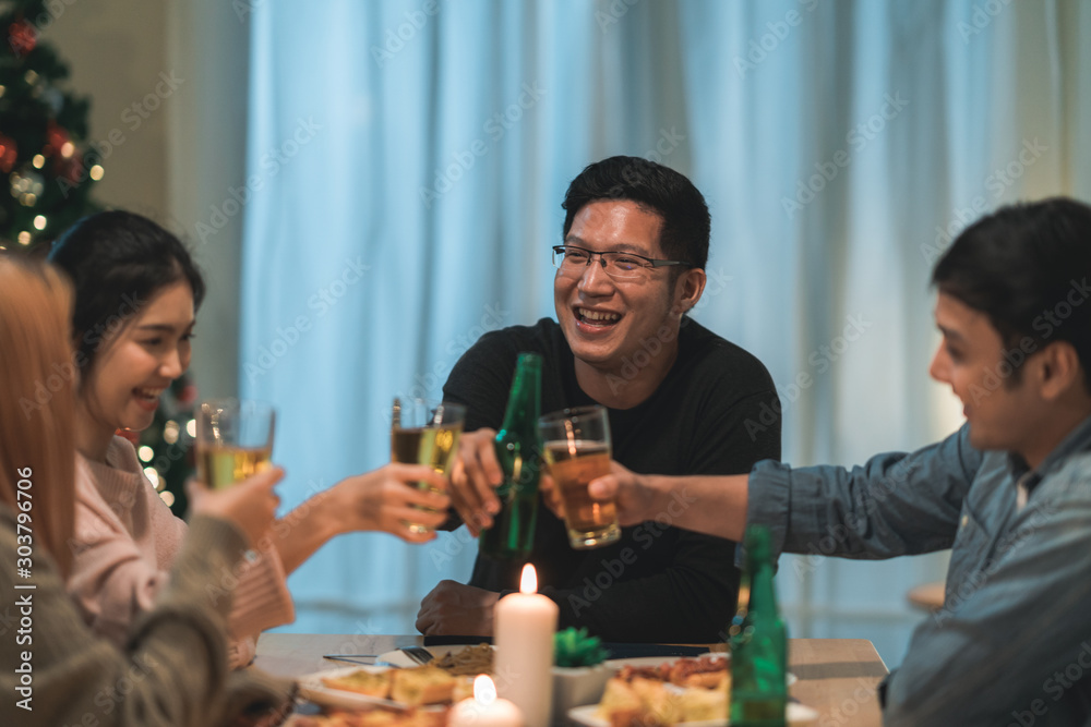 Fototapety, obrazy: Merry Christmas and Happy New Year! Young friends group having dinner at home. Asian family party with beer and pizza food near christmas tree at house in night. Celebration holiday and togetherness.