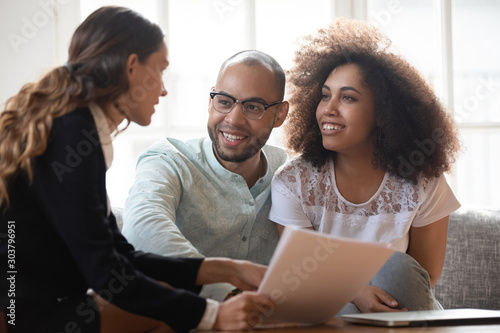 Young african american family couple meeting mixed race agent. Canvas Print