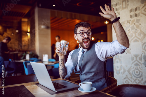 Fotomural  Attractive caucasian bearded businessman in suit and with eyeglasses holding glass of water and waving while sitting in cafe