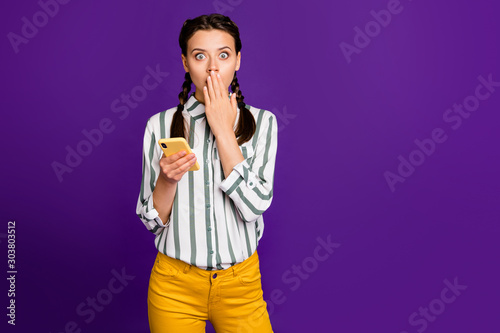 Photo of beautiful lady holding telephone hiding mouth hand reading negative comments awful situation wear striped shirt yellow trousers isolated purple color background