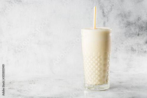 Banana oats smoothie or vanilla milkshake in glass on bright marble background. Overhead view, copy space. Advertising for milkshake cafe menu. Horizontal photo.