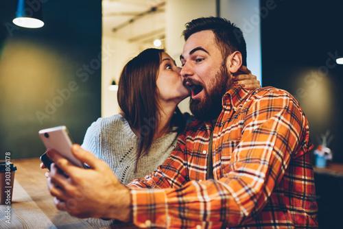 Fototapeta  Happy young woman kisses her bearded boyfriend who won prize in internet lottery