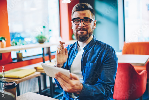 Valokuvatapetti Half length portrait of excited hipster man hoping for luck in internet contest holding digital tablet and waiting on winning results