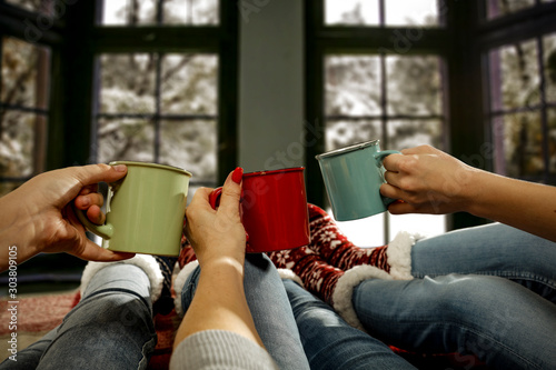 Woman legs with jeans and christmas socks.Wooden retro window with winter landscape and snow flakes.Free space for your decoration and copy space.Xmas time and cold day
