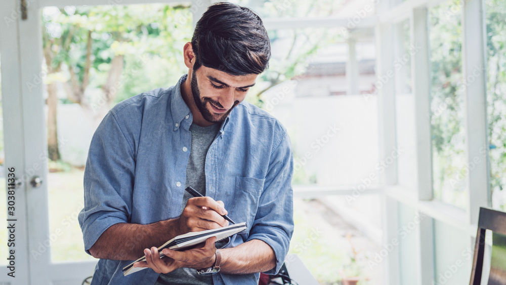 Fototapeta Young man writing on note book
