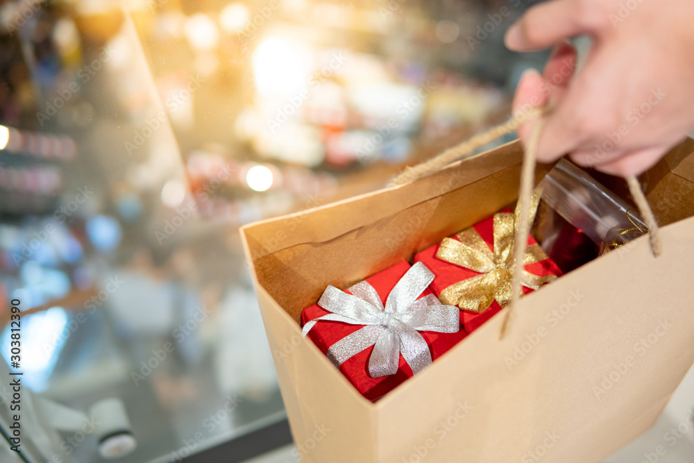 Fototapeta Male hand holding paper shopping bag with red gift boxes inside at Christmas event in department store. Buying present for Xmas holiday and New Year celebration concept