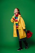 Redhead Woman In Yellow Raincoat Holding Umbrella.