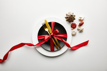 Top View Of White And Black Plates With Cutlery And Ribbon Near Festive Christmas Baubles On White Background