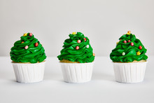 Tasty Christmas Tree Cupcakes In Row On White Surface Isolated On Grey