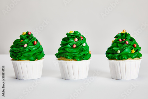 Photo tasty Christmas tree cupcakes in row on white surface isolated on grey