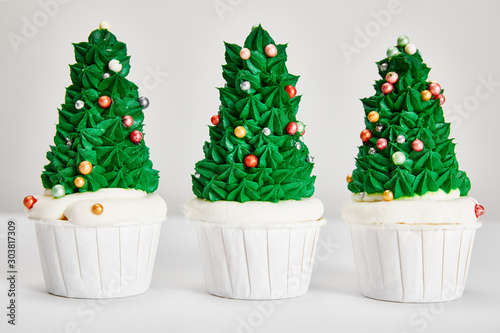 Photo delicious Christmas tree cupcakes in row on white surface isolated on grey