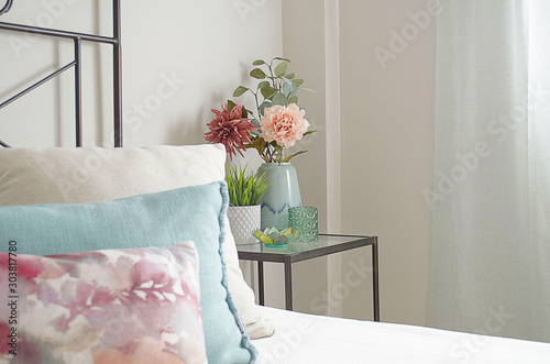 Closeup of a decorative bedside table with artificial flowers in a bright bedroom Canvas Print