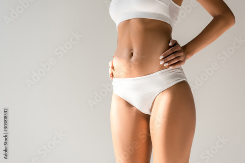 Fototapeta cropped view of slim woman in underwear posing with hands on hips isolated on gr