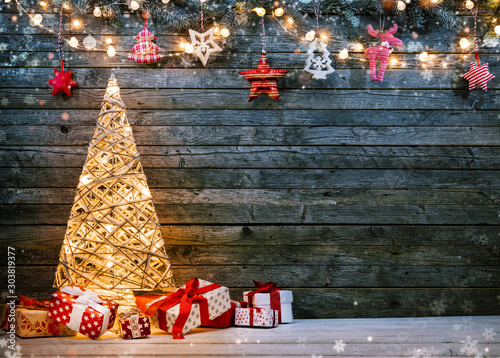 Fototapeta Holidays background with illuminated Christmas tree, gifts and decoration