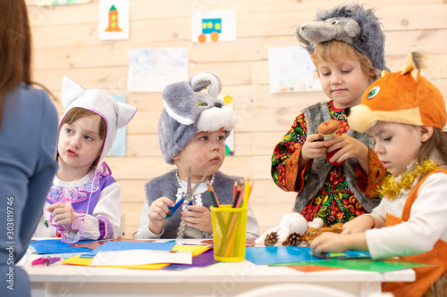 Obraz Kids with teacher make hands crafts in kindergarten. Children prepare to christmas holiday. Group of preschoolers on lesson in classroom - fototapety do salonu