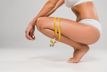 Cropped View Of Beautiful Slim Woman In Underwear Sitting On Tiptoe With Measuring Tape On Grey Background