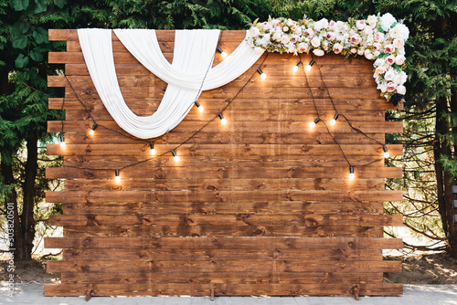 Obraz Rustic wooden wedding arch with retro garland decorated with flowers for wedding ceremony newlyweds - fototapety do salonu