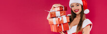 Smiling Sexy Beautiful Santa Girl Holding Gift Boxes Isolated On Burgundy, Panoramic Shot